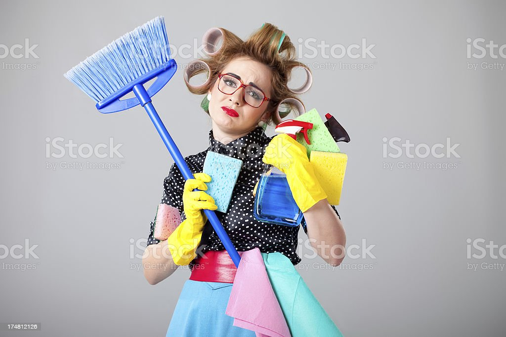 Sad nerdy housewife holding house cleaning equipment stock photo