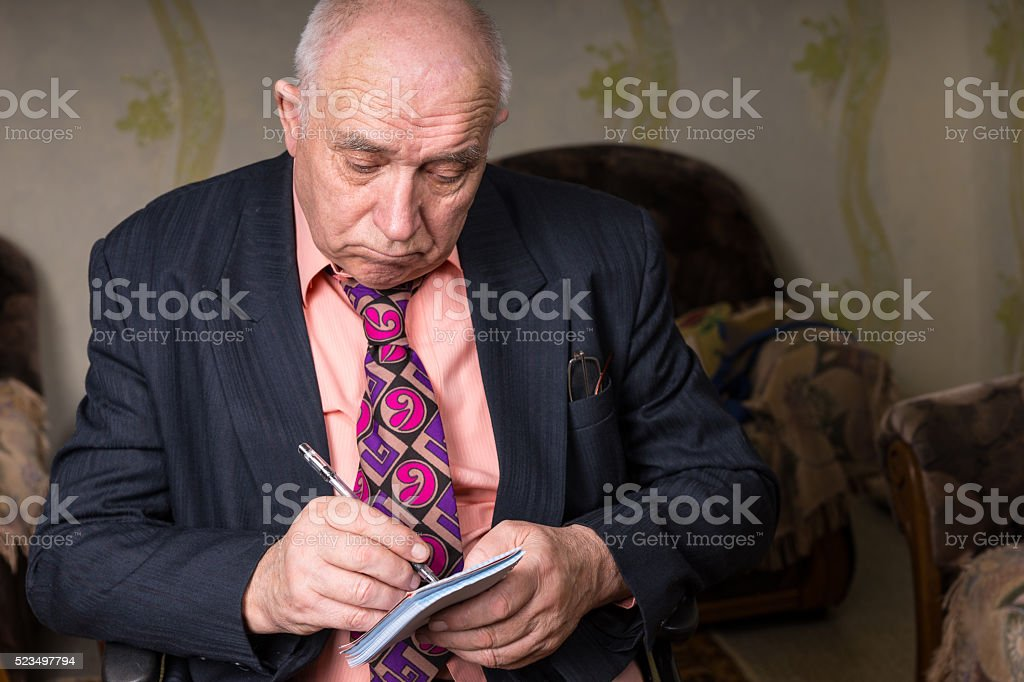 Sad Old Businessman Writing on his Small Notes stock photo