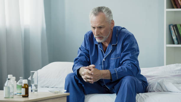 Sad old man sitting in bed and looking at pills, medication and healthcare Sad old man sitting in bed and looking at pills, medication and healthcare, stock footage urinary system stock pictures, royalty-free photos & images
