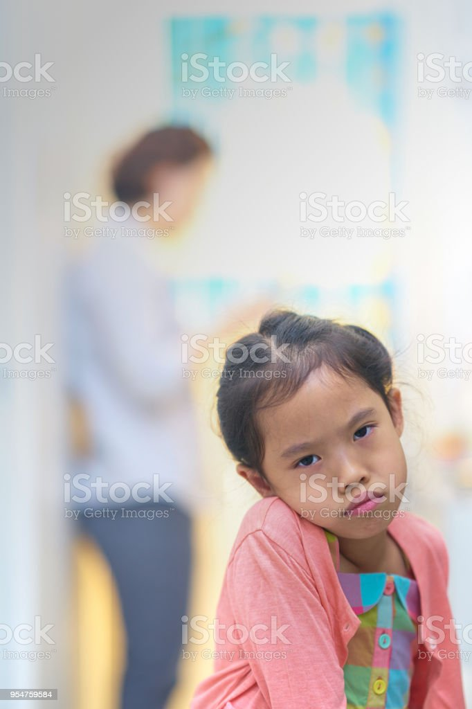 Sad or angry face small girl on mommy busy in smart phone stock photo