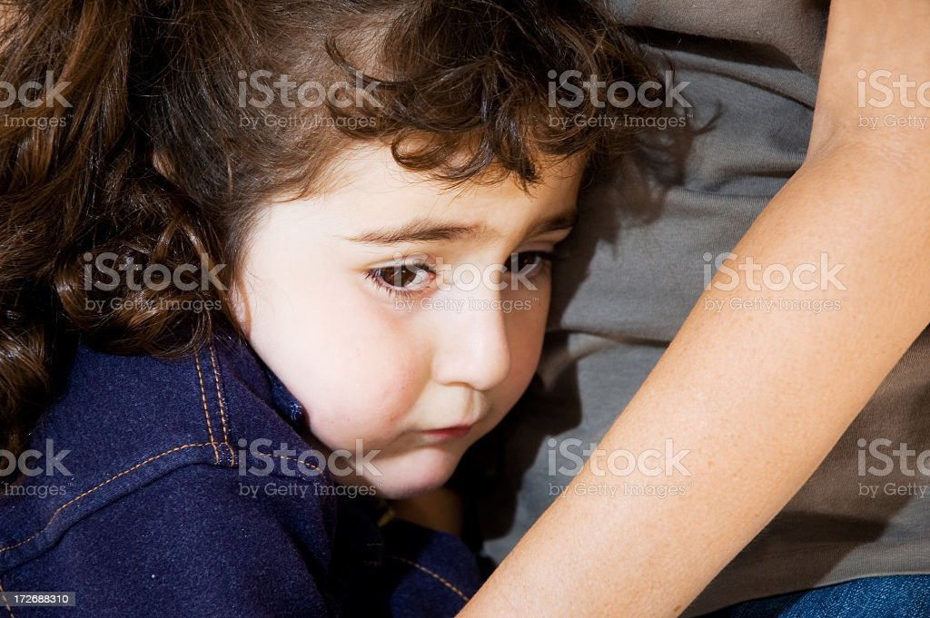 A sad or scared young girl being comforted by her mother royalty-free stock photo