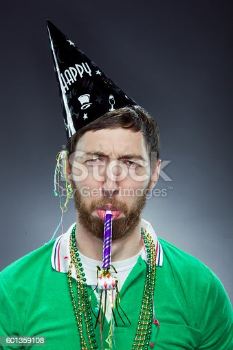 Studio Portrait of a man having a bad attitude about the party. He is in his late 20s with fun party toys (necklace, party blower, and party hat) looking sad.