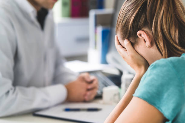 sad patient visiting doctor. young woman with stress or burnout getting help from medical professional or therapist. anxiety, depression or mental health problems concept. - victim stock pictures, royalty-free photos & images