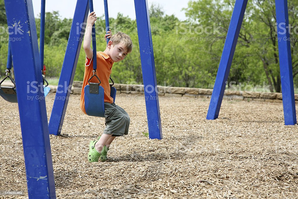 Sad Preschool Boy Swinging at the Playground with Copy Space royalty-free stock photo