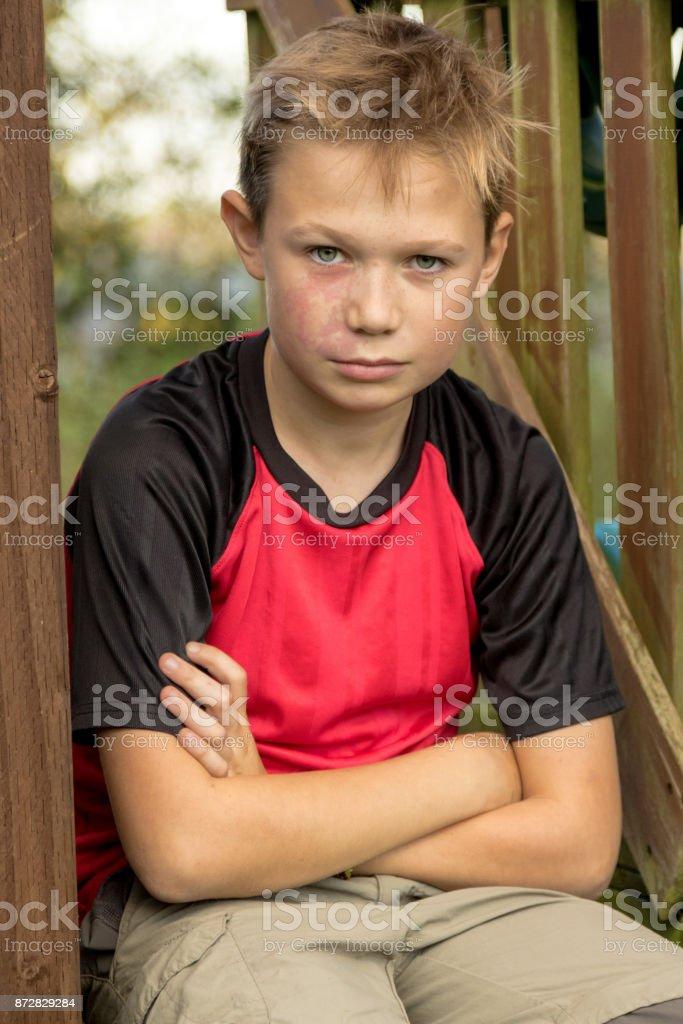 Sad pre-teen boy sitting outside stock photo