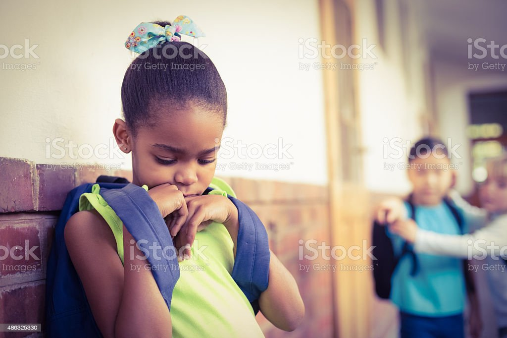 Sad pupil being bullied by classmates at corridor stock photo