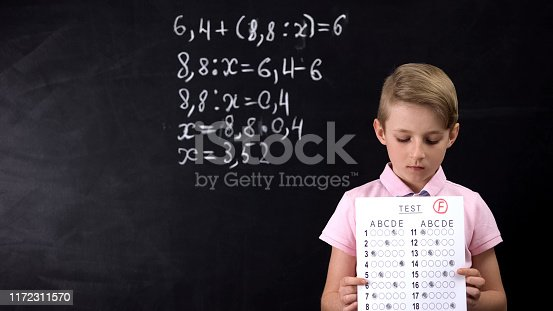 istock Sad pupil holding failed test against blackboard background, lack of knowledge 1172311570