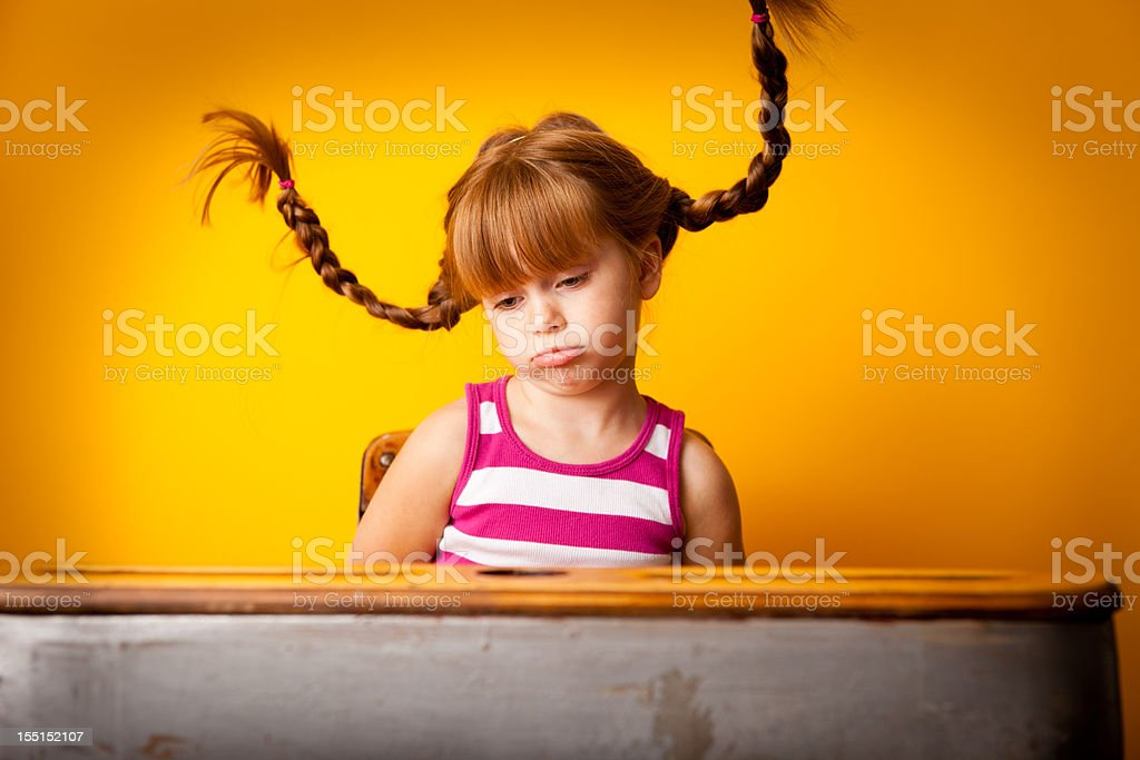 Sad Red-Haired Girl with Upward Braids and Pouty Lip royalty-free stock photo