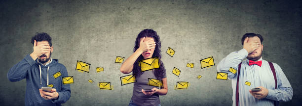 Sad regretful people men and woman sending emails via mobile phone covering with hand their faces stock photo