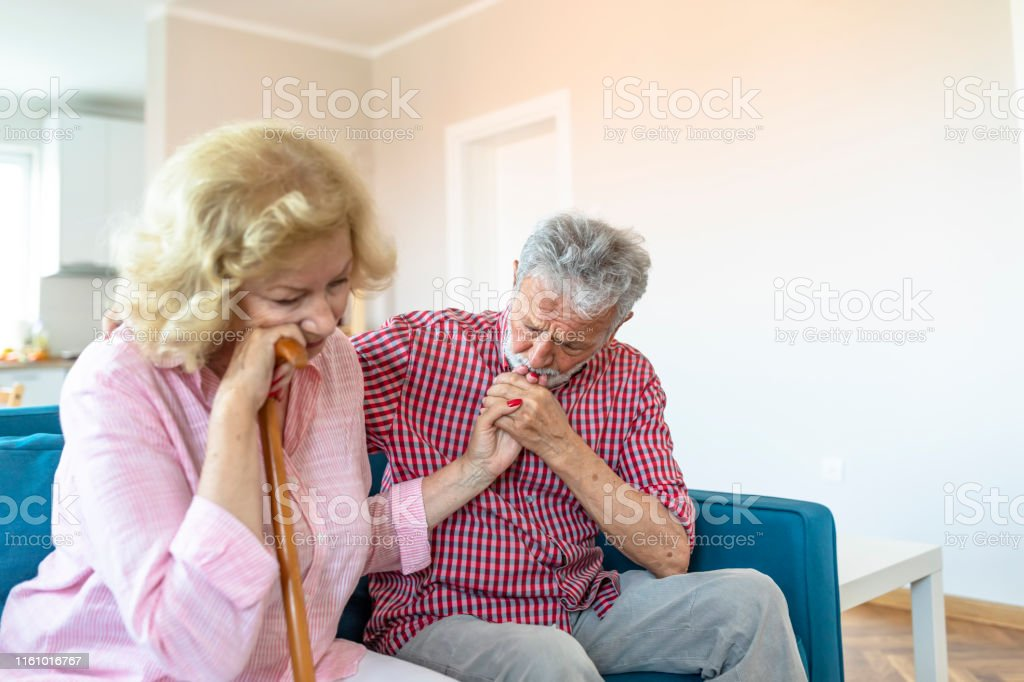 Thoughtful senior woman with grey hair sitting on sofa in living...