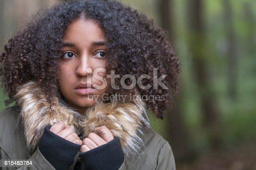 Beautiful mixed race African American girl teenager female young woman outside in a forest looking scared sad depressed or thoughtful