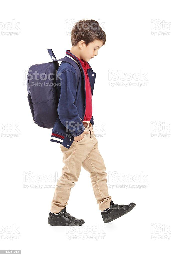 Sad school boy walking stock photo