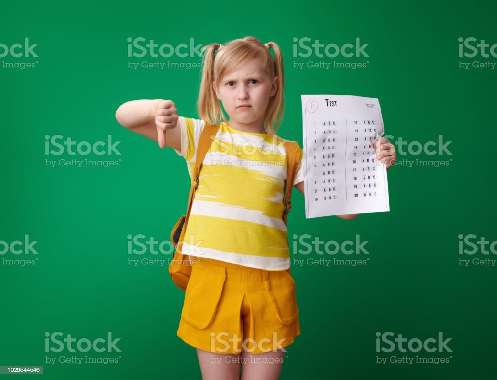 sad school girl with backpack with a bad grade test showing thumbs...