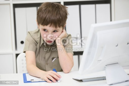istock Sad schoolboy does homework. Upset boy behind desk with pen and notebook.The little boy thinks over the task 1148622842