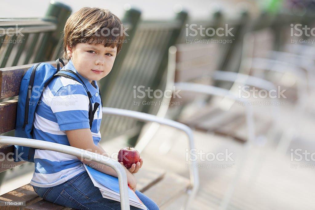 sad schoolboy in the schoolyard sitting on bench stock photo