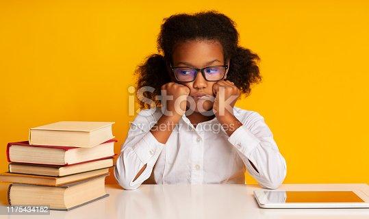 istock Sad schoolgirl sitting between tablet computer and books, studio shot 1175434152