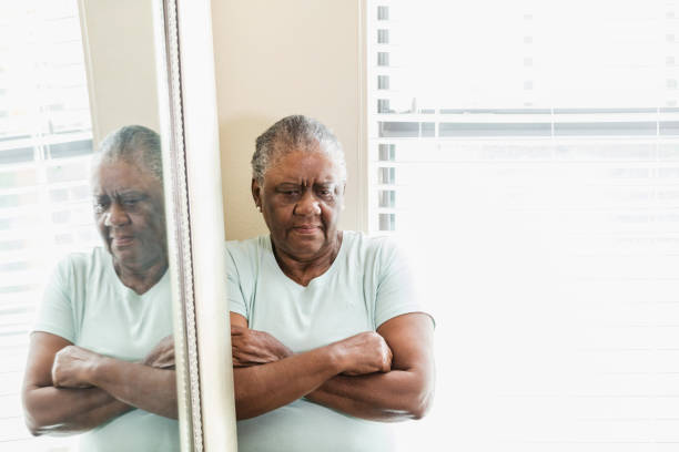 Sad senior African-American woman, arms crossed A serious senior African-American woman at home, standing by a window and mirror, looking down with arms crossed. She is lonely and depressed. low self esteem stock pictures, royalty-free photos & images