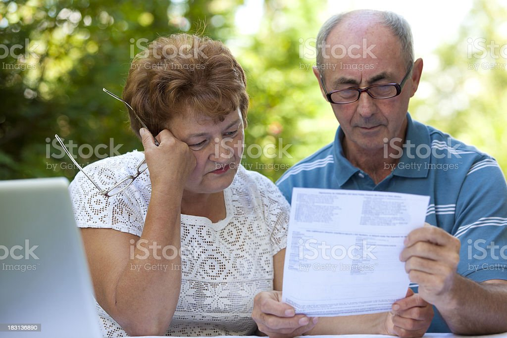 Sad senior couple goes over bills royalty-free stock photo