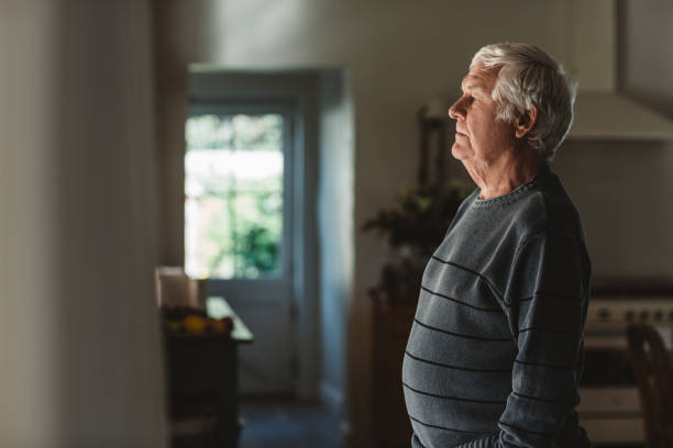 Sad senior man looking out through a window at home stock photo