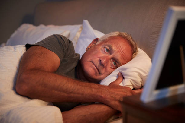 Fotoğraf çerçevesi seyir yatakta yatan üzgün üst düzey adam stok fotoğrafı
