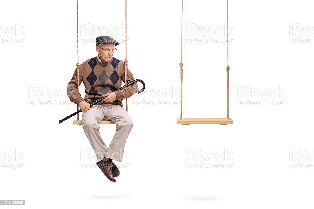 Sad senior sitting on a swing stock photo