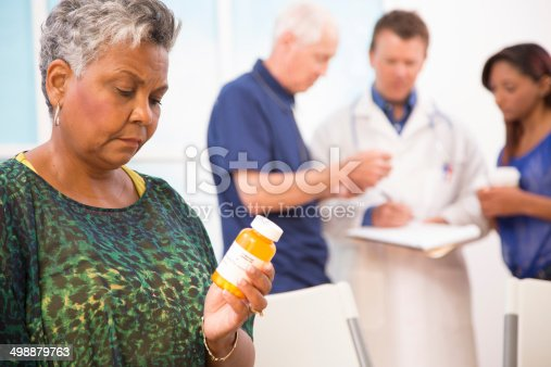 istock Sad senior woman abuses prescription medications. Doctor, patients background. 498879763