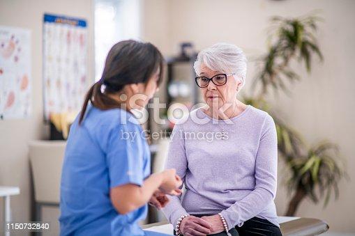 istock Sad senior woman at doctor's office 1150732840