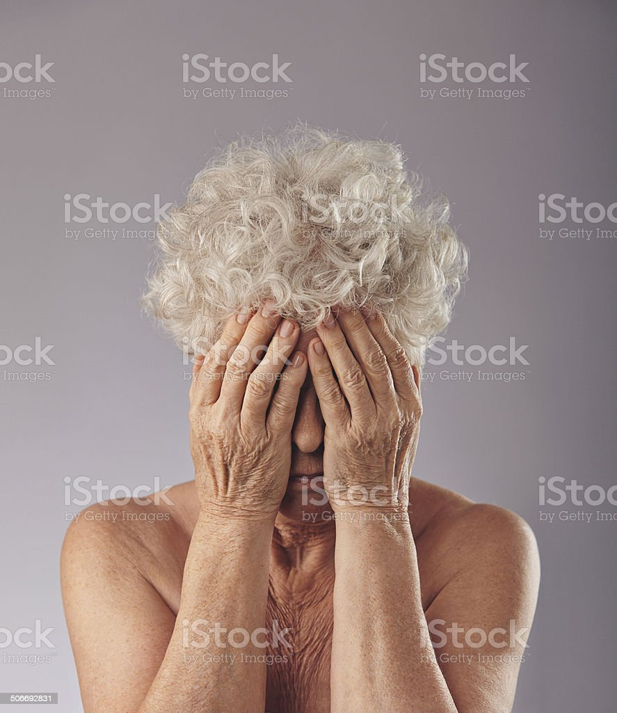 Sad senior woman covering her face stock photo