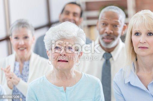 487670635istockphoto Sad senior woman is emotional during seniors meeting 672597026