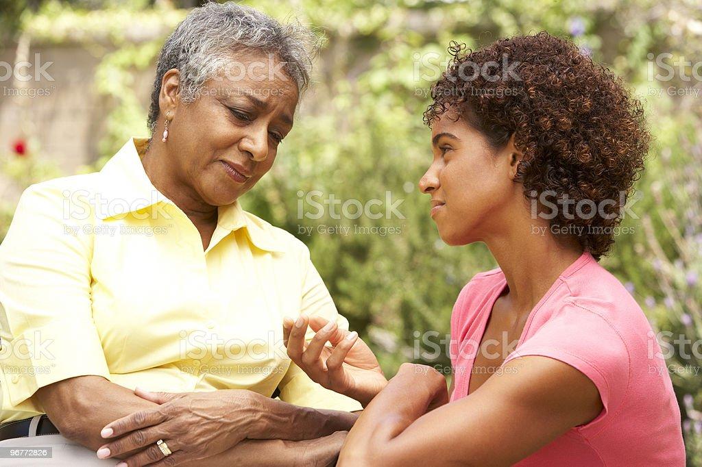 Sad Senior woman listening to adult daughter stock photo