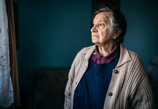 Sad senior woman looking out of window stock photo