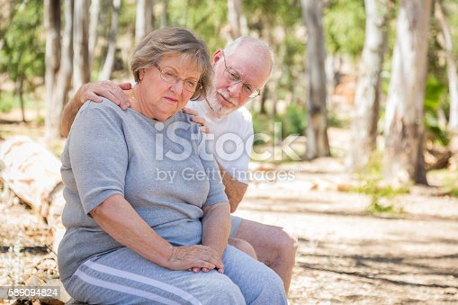 istock Sad Senior Woman Sits With Concerned Husband Outdoors 589094824