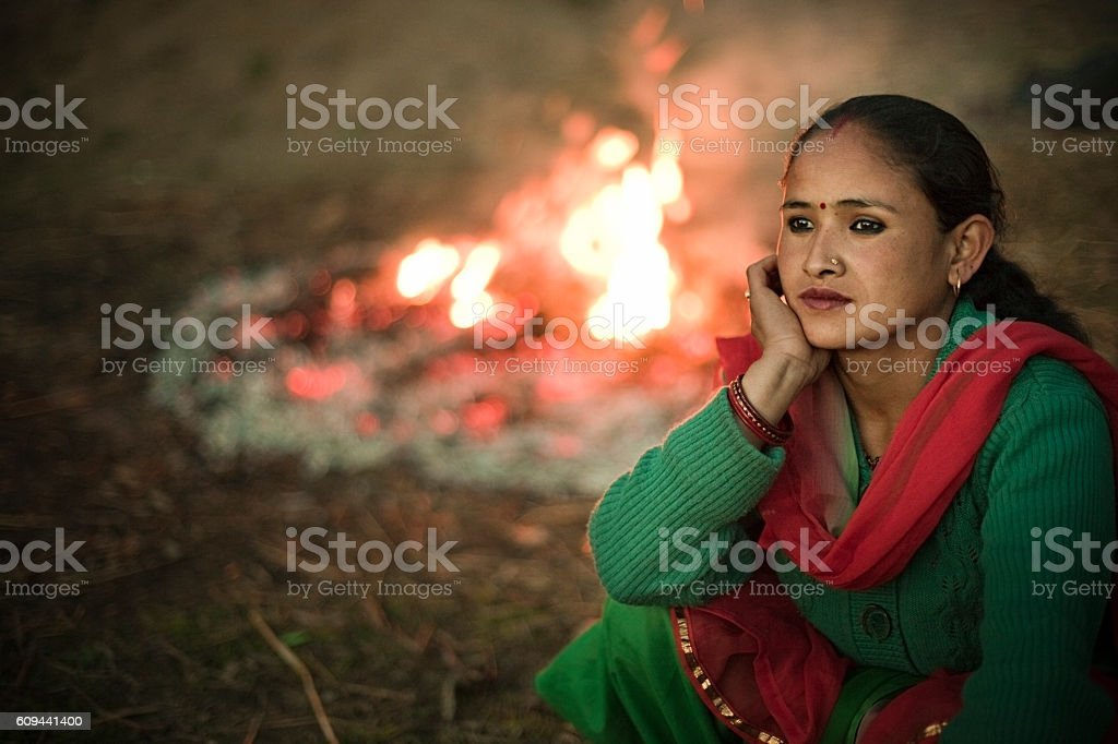 Sad serene Asian woman sitting outdoor near bonfire in evening. stock photo