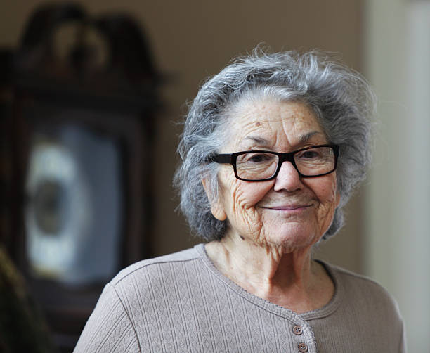 Sad Smile Senior Woman A real person senior woman standing in front of her grandfather clock at home has a sad smile. grandmother stock pictures, royalty-free photos & images