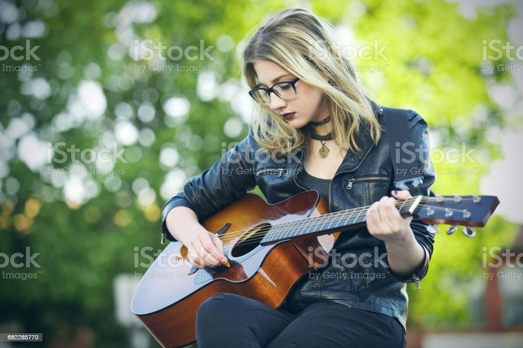 Sad Song A beautiful 15 year old girl playing a sad song on her acoustic guitar. 14-15 Years Stock Photo