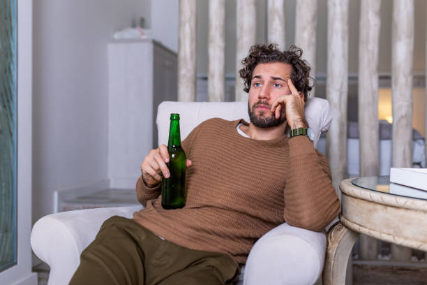 Sad sports fan sitting in an sofa and watching a match on television with his team losing the game . man watching football or soccer game on tv at home and drinking beer Sad sports fan sitting in an sofa and watching a match on television with his team losing the game . man watching football or soccer game on tv at home and drinking beer man cave couch stock pictures, royalty-free photos & images