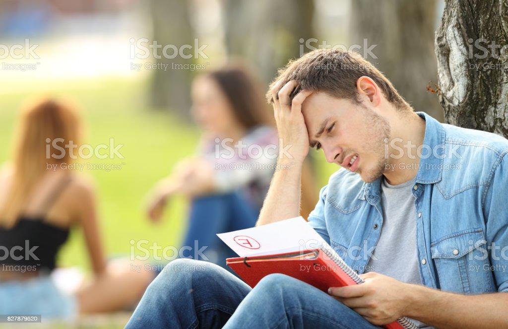 Sad student checking a failed exam stock photo