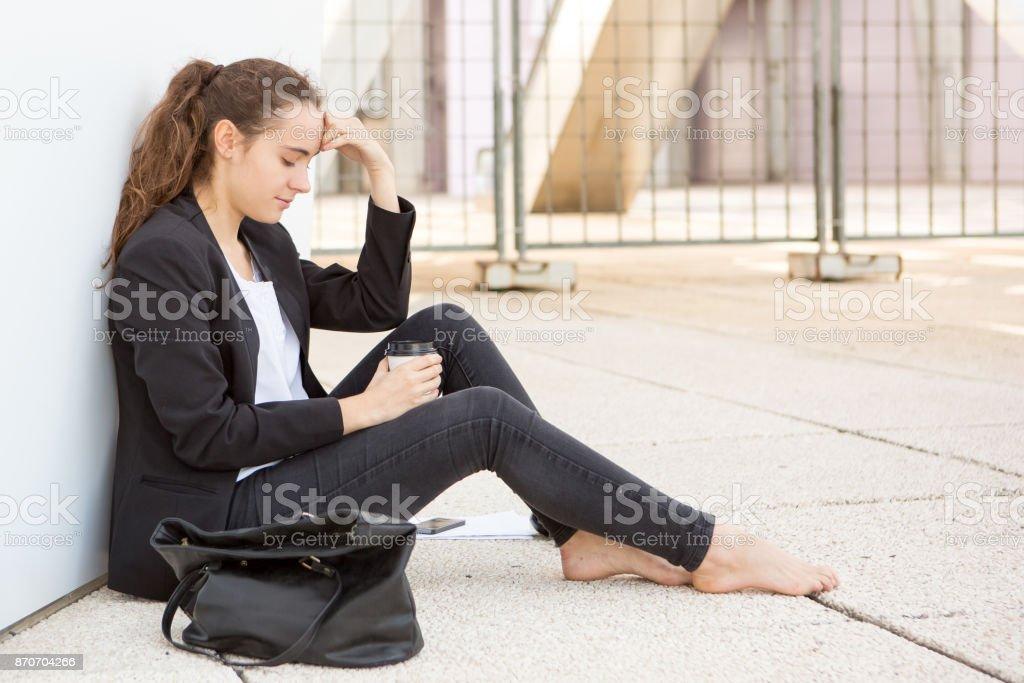 Sad student girl sitting on ground стоковое фото