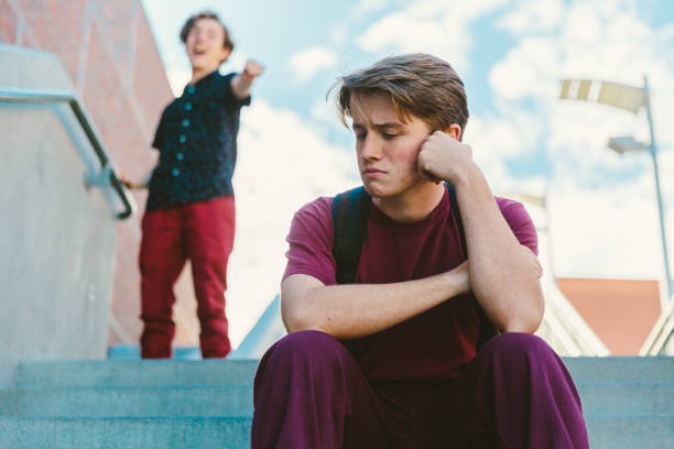 Sad student sitting on staircase is bullied by laughing boy stock photo
