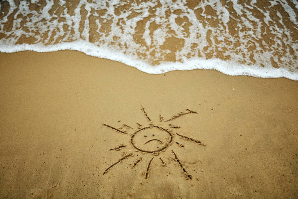 Sad symbol of sun in the sand - summertime is over. stock photo