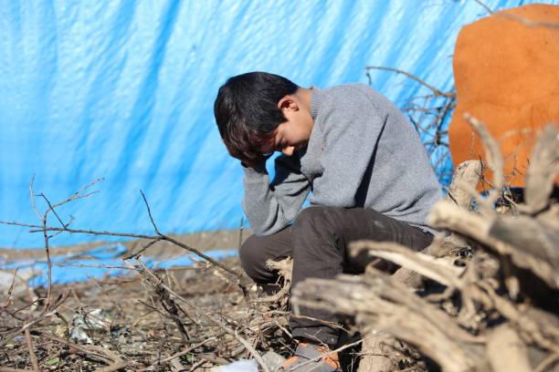 traurig syrischen kleinen jungen im flüchtlingslager - konflikt stock-fotos und bilder