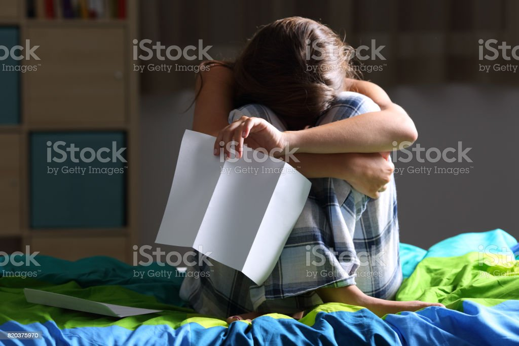 Sad teen after reading a letter stock photo