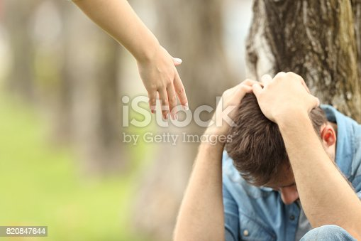 istock Sad teen and a hand offering help 820847644