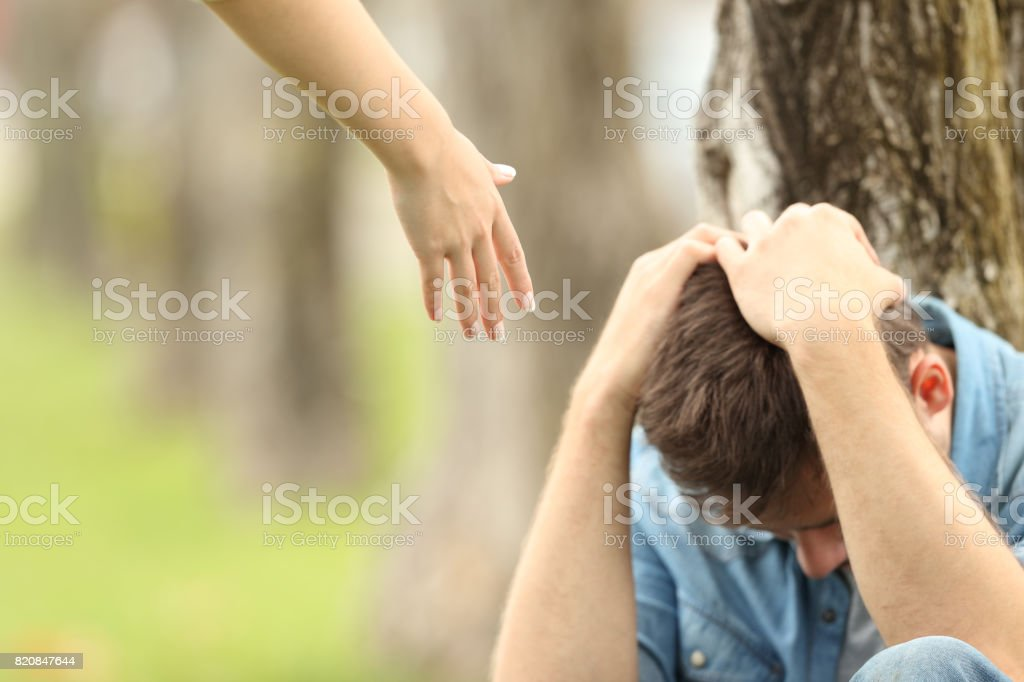 Sad teen and a hand offering help stock photo