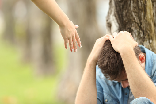 Sad Teen And A Hand Offering Help Stock Photo - Download Image Now