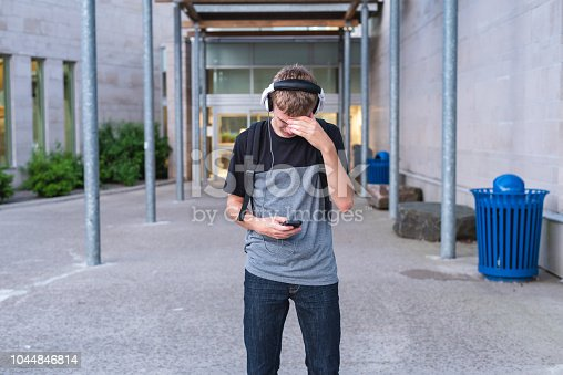 811258918 istock photo Sad teen covering his face while standing in front of his school and listening to music. 1044846814