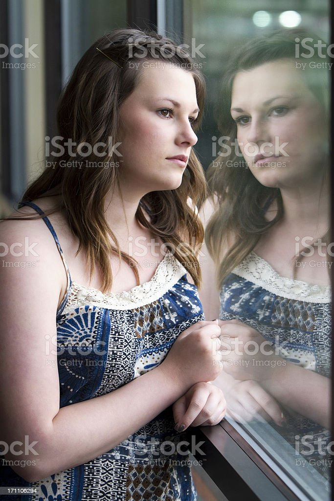 Sad Teen Girl Looking Out Window stock photo