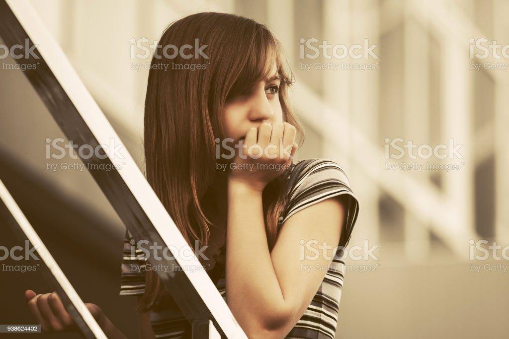 Sad teen girl on steps against a school building stock photo