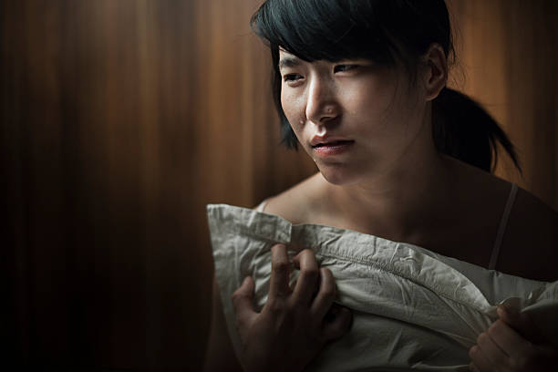 Sad teenage Asian girl crying with tears holding pillow. Indoor low key image of a lonely cute teenage Asian girl crying with tears by holding and pressing a plane white pillow with her chest and looking away. Horizontal composition with copy space and selective focus. spaghetti straps stock pictures, royalty-free photos & images