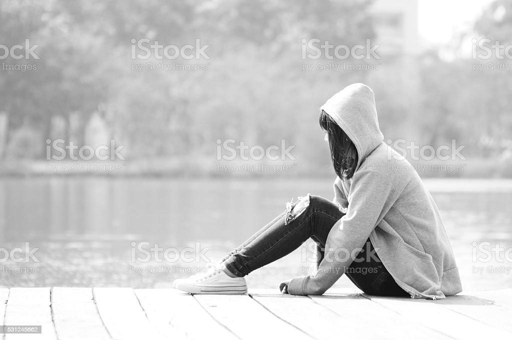 Sad teenage girl sitting alone near river stock photo